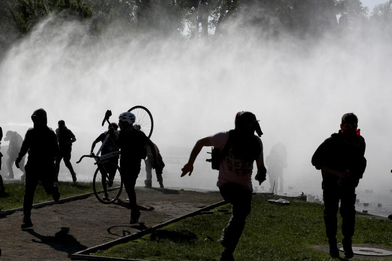 Demonstrators run from tear gas launched by police as a state of emergency remains in effect in Santiago, Chile, Sunday, Oct. 20, 2019. Protests in the country have spilled over into a new day, even after President Sebastian Pinera cancelled the subway fare hike that prompted massive and violent demonstrations. (Photo: Esteban Felix/AP)