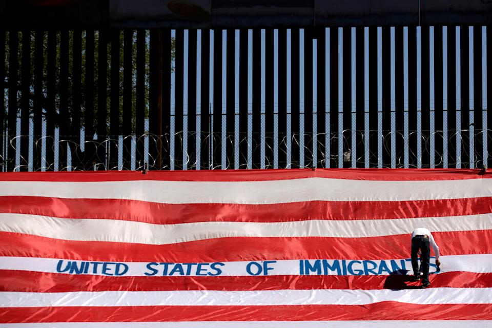 Roberto Marquez, known as Roberz, writes on a large U.S. flag as part of a protest called 'United States of Immigrants', aimed to demand respect for the migrants, near a border wall in El Paso, Texas, as pictured from Ciudad Juarez, Mexico June 6, 2019. REUTERS/Jose Luis Gonzalez     TPX IMAGES OF THE DAY