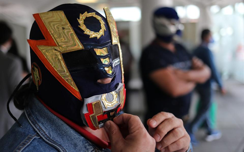 """A masked wrestler """" Super Elektra"""" and fellow wrestler """"Rayo Del Bajio"""" are pictured before they receive food parcels donated by a local supermarket to wrestlers who are facing hard times as the coronavirus - REUTERS/Henry Romero"""