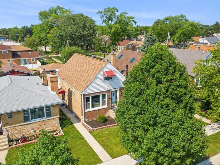 an aerial view of a neighborhood with the house for sale near chicago in the middle on a tree lined street
