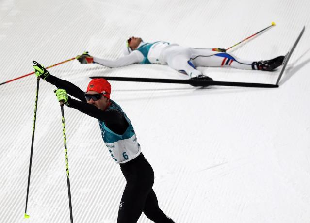 Nordic Combined Events - Pyeongchang 2018 Winter Olympics - Men's Individual 10 km Final - Alpensia Cross-Country Skiing Centre - Pyeongchang, South Korea - February 20, 2018 - Fabian Riessle of Germany celebrates as Jarl Magnus Riiber of Norway lies down after the finish line. REUTERS/Carlos Barria