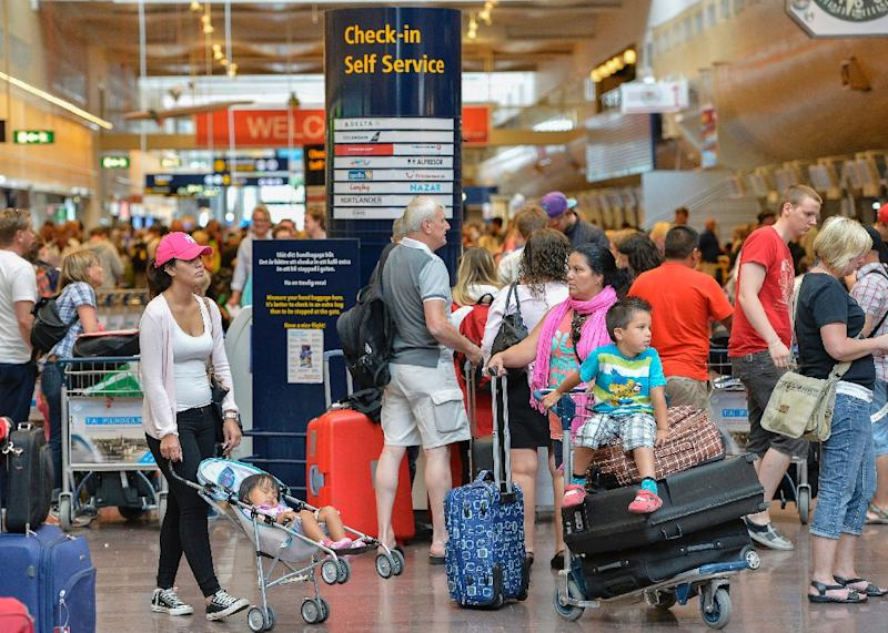 Travellers wait in the terminal building at Stockholm's Arlanda on August 17, 2013