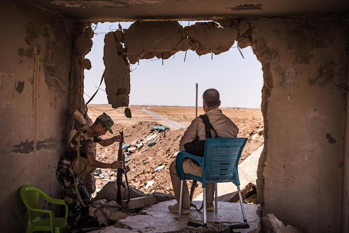 Members of the Iranian-backed militias, known as the Popular Mobilization Forces, watch the road at the Syrian border outside Al Badi, Iraq, June 17, 2017. (Sergey Ponomarev/The New York Times)