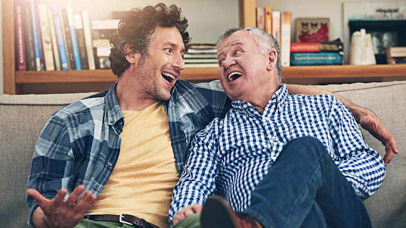 Shot of a mature man and his elderly father sitting on the sofa at home and having a chat.
