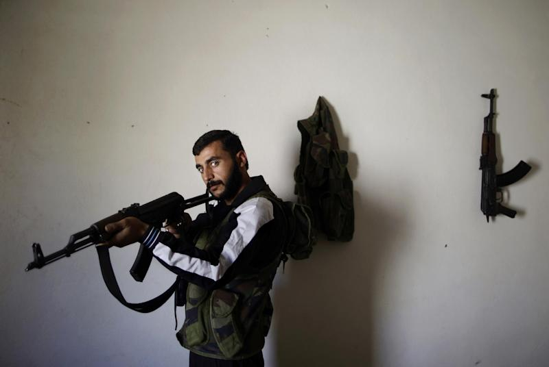 In this Wednesday, Sept. 5, 2012, photo, Syrian rebel fighter, Hamzah Alhassan, 25, a former blacksmith, poses for a picture at a house where he and others wait their turn to go and fight against government forces in Aleppo, in Marea on the outskirts of Aleppo city, Syria. Syria's rebels have turned to a new tactic of attacking bases, trying to stop the jets and attack helicopters that have wreaked devastation on their fighters and civilians in the battleground city of Aleppo and the nearby countryside.(AP Photo/Muhammed Muheisen)