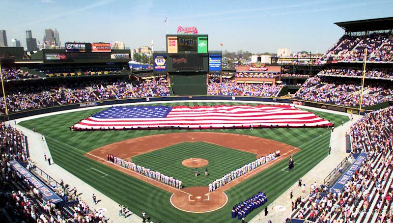 FILE - In this April 5, 1999 file photo, The Atlanta Braves, right, and the Philadelphia Phillies line the base paths as a giant American flag is stretched across the outfield while the national anthem is played before the start of their opening-day game in Atlanta. The Atlanta Braves are leaving Turner Field and moving into a new 42,000-seat, $672 million stadium complex in Cobb County in 2017. Braves executives John Schuerholz, Mike Plant and Derek Schiller said Monday, Nov. 11, 2013, that the team decided not to seek another 20-year lease at Turner Field and began talks with the Cobb Marietta Coliseum and Exhibit Hall Authority in July. (AP Photo/John Bazemore, Fle)
