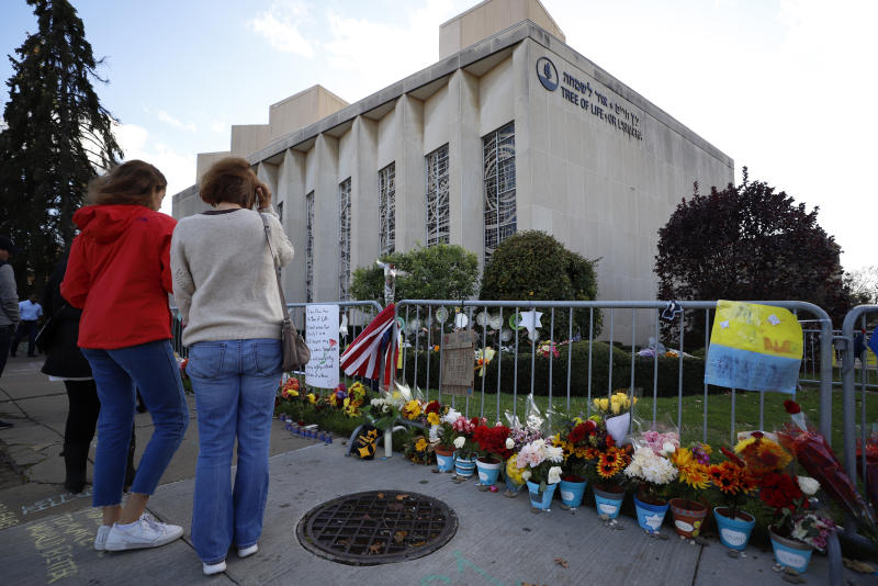 Passersby stop to pay respect outside the Tree of Life synagogue in Pittsburgh on Sunday, Oct. 27, 2019, the first anniversary of the shooting at the synagogue, that killed 11 worshippers. (AP Photo/Gene J. Puskar)