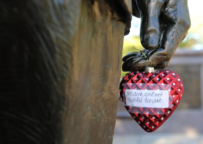 A heart ornament placed in tribute to former President George H.W. Bush hangs off a hand at the Bush monument in Houston on Dec. 1. (Photo: Thomas B. Shea/AFP/Getty Images)