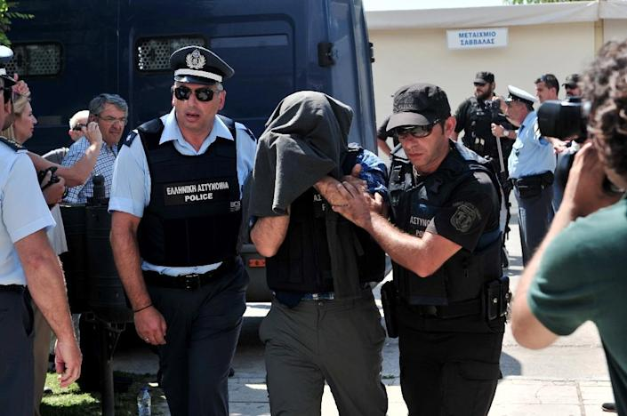 A Turkish officer who fled after the coup is escorted by police officers into the courthouse of Alexandroupoli, northern Greece, on July 21, 2016, to face trial for illegal entry (AFP Photo/Sakis Mitroldis)