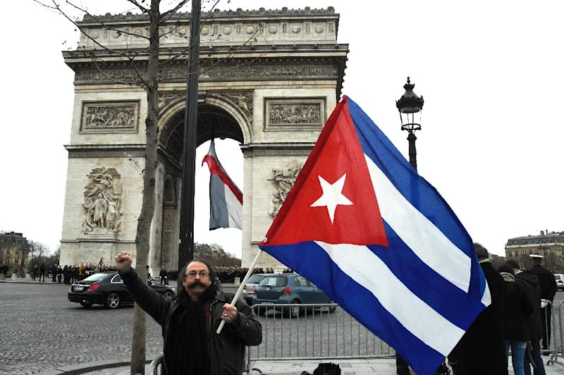 A man holds a Cuban flag at the Arc de Triomphe in Paris on Febuary 1, 2016 (AFP Photo/Dominique Faget)