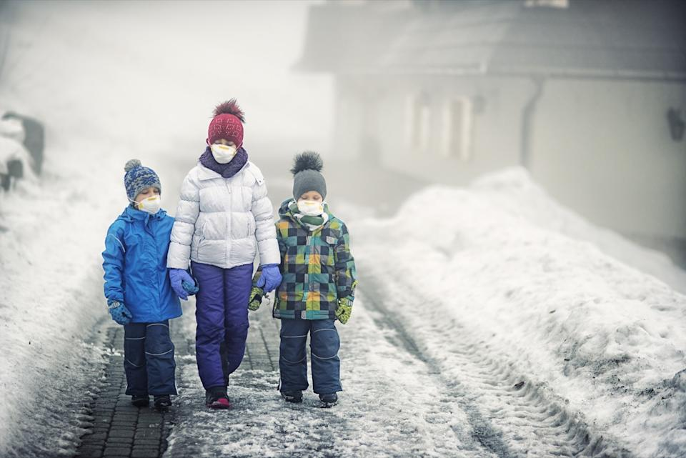 Kids wearing pollution masks walking on dirty snow. The air is thick with mist and smog.