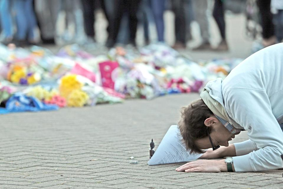 A man prays next to floral tributes at Leicester City (Aaron Chown/PA Wire)