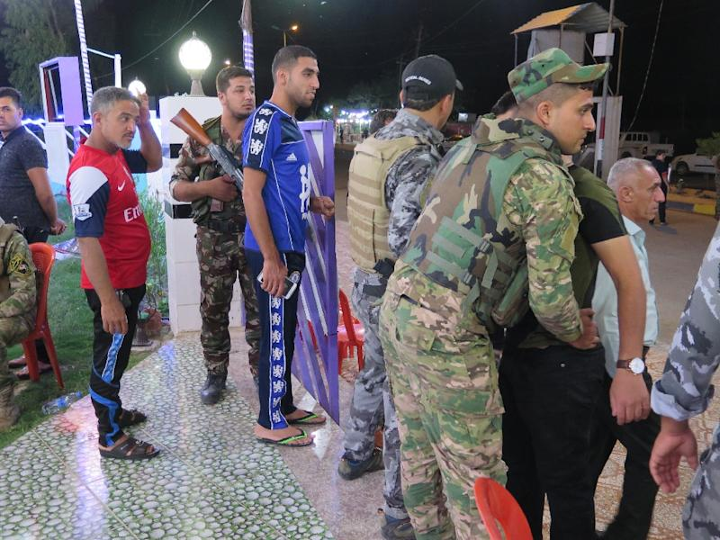 Members of the Iraqi security forces frisk young men during a memorial ceremony at the Al-Furat cafe in Balad, 80 km north of Baghdad, ahead of the Champions League final between Real Madrid and Atletico Madrid (AFP Photo/Jean-Marc Mojon)