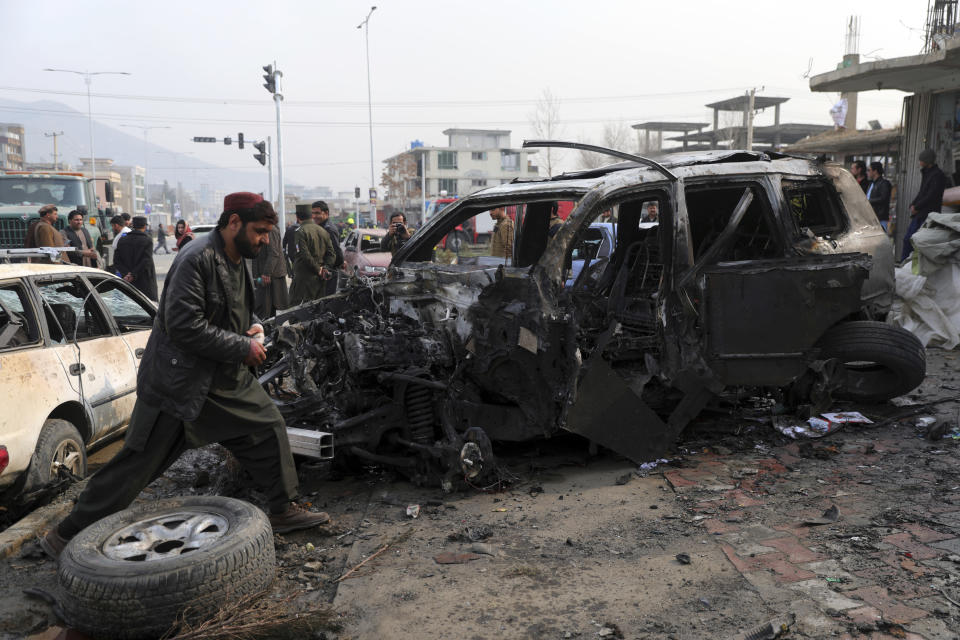 People gather near the site of a deadly bombing attack in Kabul, Afghanistan, Sunday, Dec. 20, 2020. Afghanistan's Interior Ministry says that the car bomb blast killed at least eight people and wounded more than 15 others, including a member of parliament, Khan Mohammad Wardak. (AP Photo/Rahmat Gul)