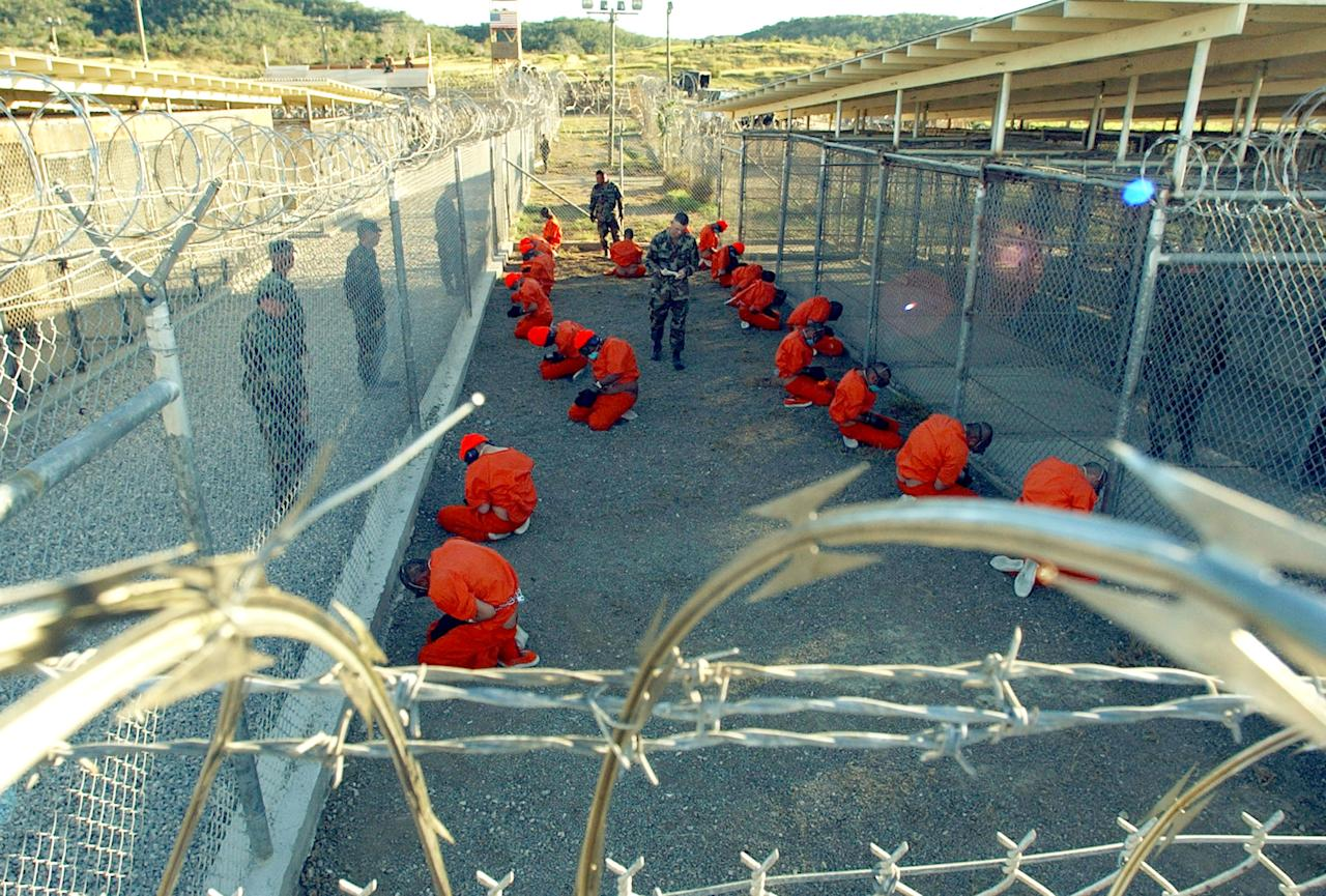 399884 01: U.S. Military Police guard Taliban and al Qaeda detainees in orange jumpsuits January 11, 2002 in a holding area at Camp X-Ray at Naval Base Guantanamo Bay, Cuba during in-processing to the temporary detention facility. The detainees will be given a basic physical exam by a doctor, to include a chest x-ray and blood samples drawn to assess their health, the military said. The U.S. Department of Defense released the photo January 18, 2002. (Photo by Petty Officer 1st class Shane T. McCoy/U.S. Navy/Getty Images)