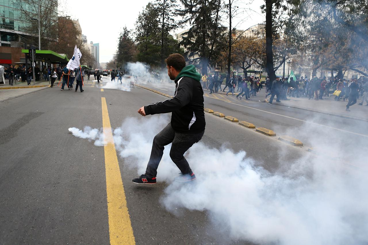 A demonstrator kicks a tear gas canister during clashes at a march called by students to request changes in the education system in Santiago, Chile September 5, 2017. REUTERS/Ivan Alvarado