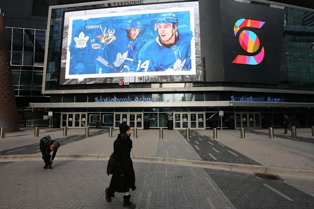 TORONTO, ON- MARCH 12 - Fans and commuters walk past Scotiabank Arena where the Toronto Maple Leafs and the Nashville Predators were supposed to play tonight. The NHL along with the NBA, MLB, NLS and MLS have suspended all games in order to slow the spread of COVID-19 in Toronto. March 12, 2020. (Steve Russell/Toronto Star via Getty Images)