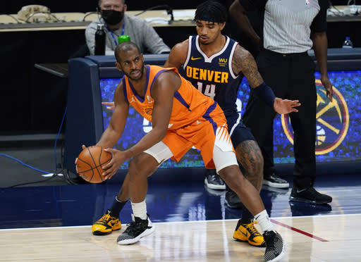Phoenix Suns guard Chris Paul, left, pulls in a loose ball as Denver Nuggets guard Gary Harris defends during the second half of an NBA basketball game Friday, Jan. 1, 2021, in Denver. The Suns won 106-103. (AP Photo/David Zalubowski)
