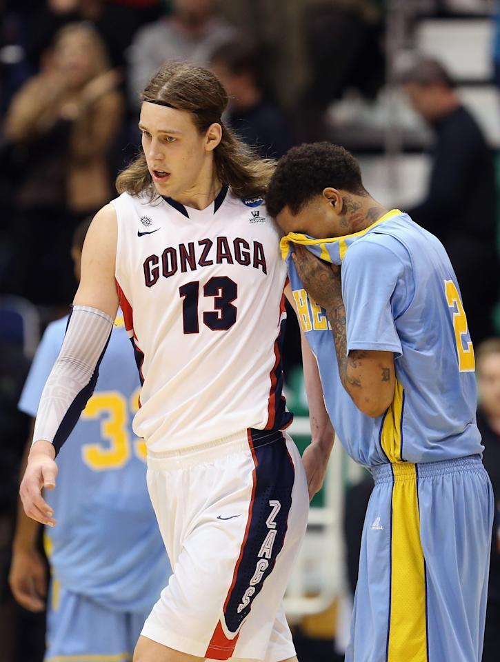 SALT LAKE CITY, UT - MARCH 21:  Kelly Olynyk #13 of the Gonzaga Bulldogs walks past Derick Beltran #2 of the Southern Jaguars after defeating them during the second round of the 2013 Men's NCAA Basketball Tournament at EnergySolutions Arena on March 21, 2013 in Salt Lake City, Utah.  (Photo by Streeter Lecka/Getty Images)