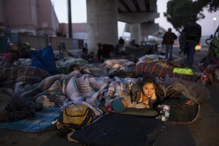 Early morning light illuminates the face of a migrant woman and her child as she wakes after sleeping under a bridge at the Chaparral border crossing in Tijuana, Mexico, Friday, Nov. 23, 2018. The mayor of Tijuana has declared a humanitarian crisis in his border city and says that he has asked the United Nations for aid to deal with the approximately 5,000 Central American migrants who have arrived in the city. (AP Photo/Rodrigo Abd)