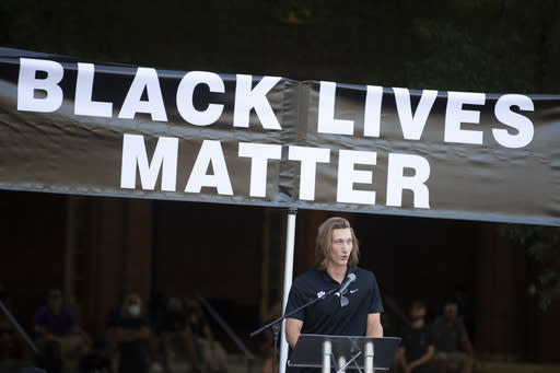 FILE - Clemson quarterback Trevor Lawrence speaks during a protest over the death of George Floyd Saturday, June 13, 2020, in Clemson, S.C. This summer college athletes have organized campus marches, threatened boycotts, and been trending on social media as if they had just scored game-winning touchdowns without stepping foot on a field. (AP Photo/John Bazemore)