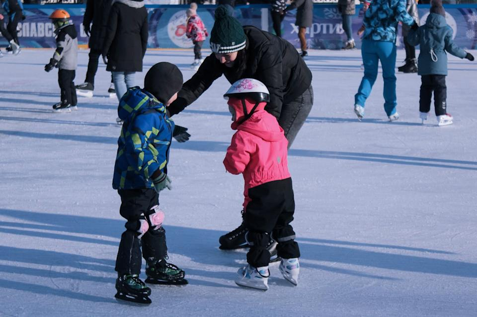 An adult bends down to talk to children; all are on ice skates on an outdoor ice rink.