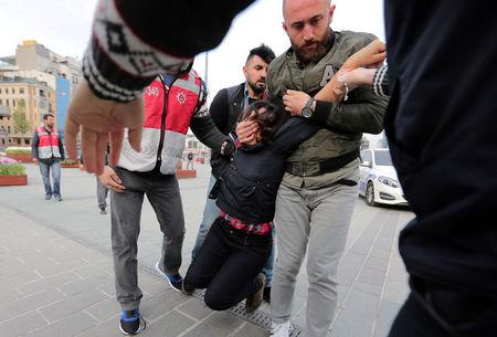 Plainclothes police officers detain a protester as she and others attempt to defy a ban and to gather at Taksim Square to celebrate May Day, in central Istanbul