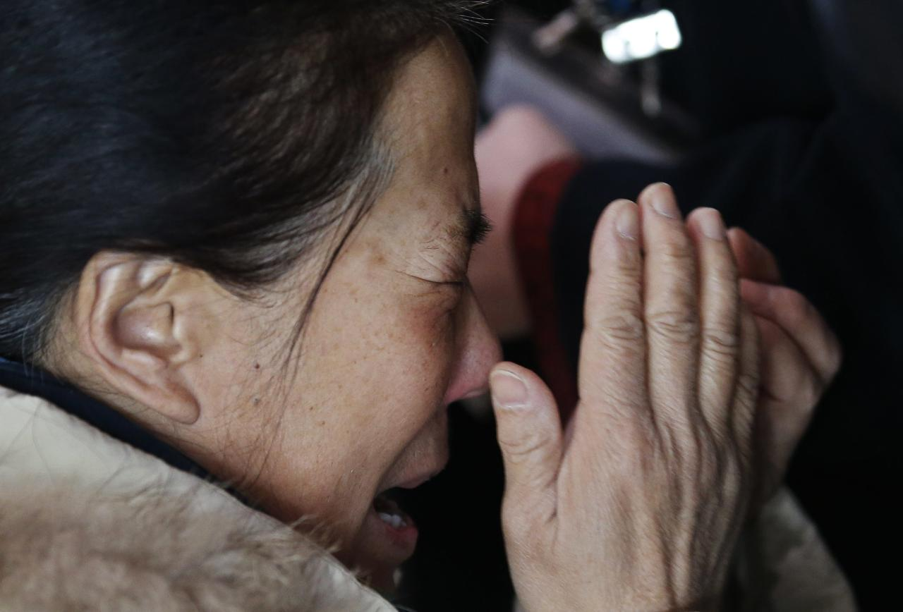 A relative of a passenger onboard Malaysia Airlines flight MH370 cries as she talks on her mobile phone at the Beijing Capital International Airport in Beijing March 8, 2014. The Malaysia Airlines flight carrying 227 passengers and 12 crew lost contact with air traffic controllers early on Saturday en route from Kuala Lumpur to Beijing, the airline said in a statement. Flight MH 370, operating a Boeing B777-200 aircraft departed Kuala Lumpur at 12.21 a.m. (1621 GMT Friday) and had been expected to land in the Chinese capital at 6.30 a.m. (2230 GMT) the same day. REUTERS/Kim Kyung-Hoon (CHINA - Tags: TRANSPORT DISASTER)