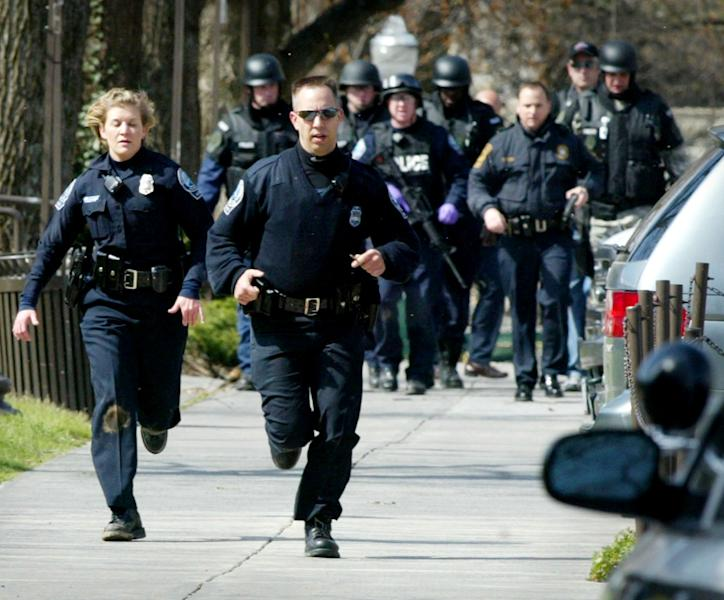 FILE - In a Monday, April 16, 2007 file photo, Blacksburg police officers run from Norris Hall on the Virginia Tech campus in Blacksburg, Va. as multiple shootings occur at the engineering building . A gunman opened fire in a Virginia Tech dorm and then, two hours later, in a classroom across campus, killing at least 30 people. Virginia's colleges and universities have quietly investigated hundreds of students, employees and others in recent years to prevent a repeat of the Virginia Tech massacre of 2007, when a student gunman left a series of increasingly disturbing warning signs before killing 32 people and himself. (AP Photo/The Roanoke Times, Matt Gentry, File) MANDATORY CREDIT