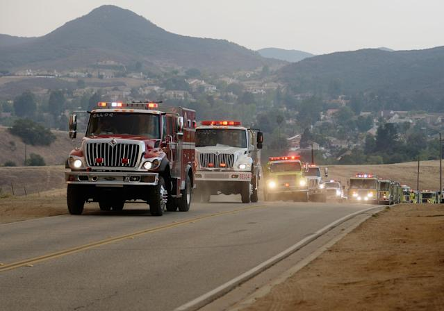NEWBURY PARK, CA - MAY 03: Fire trucks arrive to protect homes on Potrero Road as wildfire charges back up from Sycamore Canyon inside Pt. Mugu State Park on May 3, 2013 in Newbury Park, California. Hundreds of firefighters continue to battle wind and dry conditions with over 10,000 acres burned. (Photo by Kevork Djansezian/Getty Images)