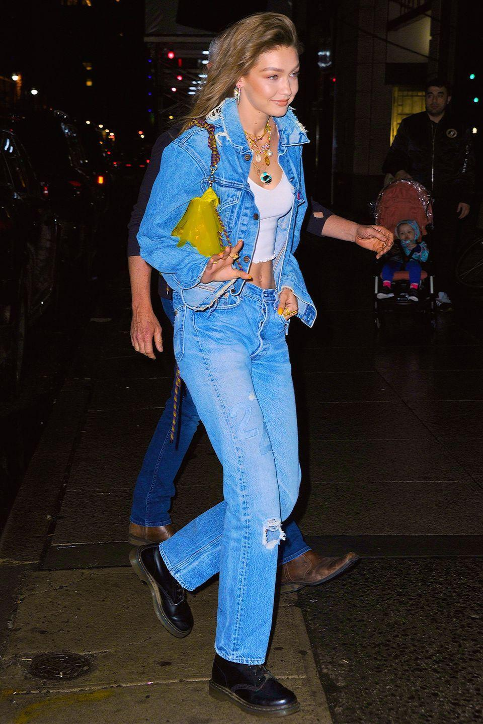 """<p>In a denim jacket, straight-leg jeans, white tank top, <a href=""""https://www.urbanoutfitters.com/shop/dr-martens-1460-smooth?adpos=1o2&cm_mmc=SEM-_-Google-_-PLA-_-383201569328_brand_urban_outfitters_x_dr_martens_product_type_womens_product_type&color=001&creative=209973910023&device=c&gclid=CjwKCAjw7_rlBRBaEiwAc23rhsQR6bzwNch2kiYqSe9WI8OMxmUpwDmu0tV6Cgnc17vZ5lVvZKO7ZxoCKtMQAvD_BwE&inventoryCountry=US&matchtype=&mrkgadid=3252904465&mrkgcl=671&network=g&product_id=33052739&utm_campaign=PLA"""" rel=""""nofollow noopener"""" target=""""_blank"""" data-ylk=""""slk:Dr. Martens boots"""" class=""""link rapid-noclick-resp"""">Dr. Martens boots</a>, layered necklaces (one of which is by <a href=""""https://www.mercii.com/products/taurus"""" rel=""""nofollow noopener"""" target=""""_blank"""" data-ylk=""""slk:Mercii"""" class=""""link rapid-noclick-resp"""">Mercii</a>), and a yellow tarnsparent bag while arriving to her birthday party in NYC. </p>"""