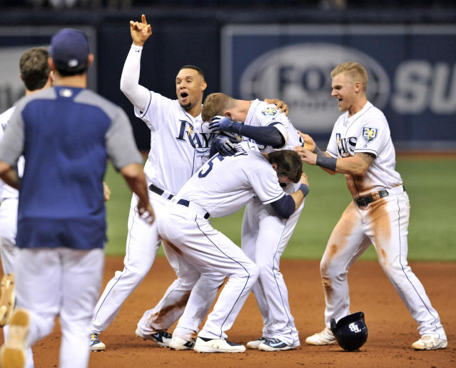Tampa Bay Rays' Carlos Gomez, left, Matt Duffy (5) and Jake Bauers, right, celebrate with Daniel Robertson, center, after his walk-off RBI-single off Detroit Tigers reliever Blaine Hardy during the 10th inning of a baseball game Monday, July 9, 2018, in St. Petersburg, Fla. The Rays defeated the Tigers 10-9. (AP Photo/Steve Nesius)