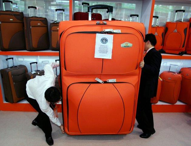 Staff members try to move a huge trolley case during the 100th Chinese Export Commodities Fair in Guangzhou, south China's Guangdong province October 15, 2006. This trolley case has been certified as the world's largest by the Guinness World Records and measures 175cm (5ft 9in) by 115cm (3ft 9.3in) by 46cm (1ft 6.1in) thick. REUTERS/Alvin Chan