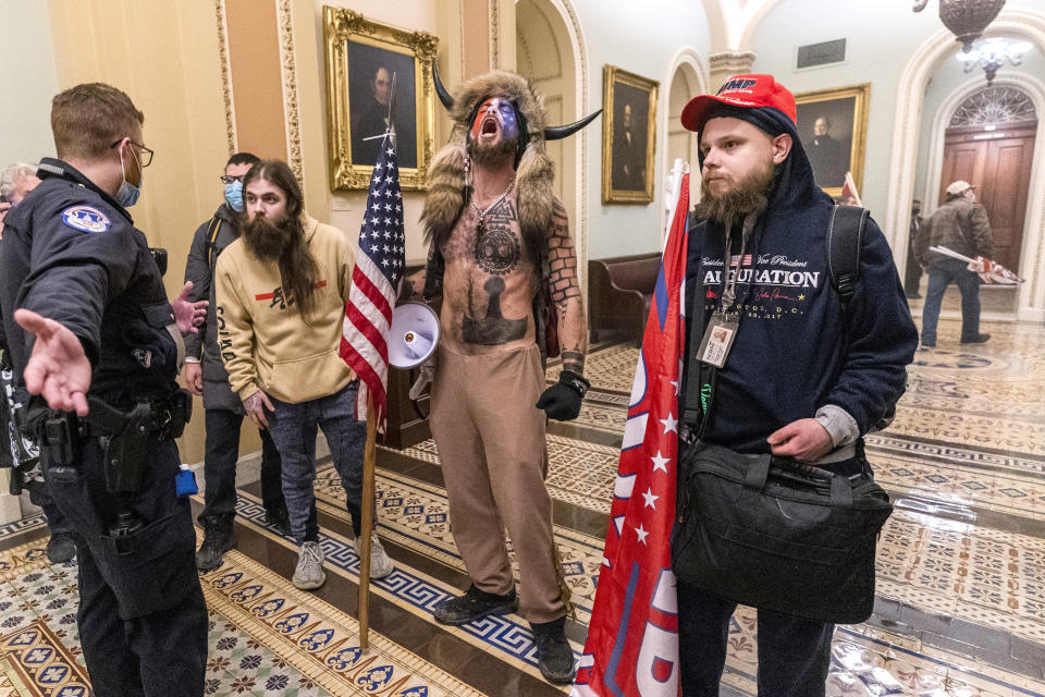 FILE - In this Wednesday, Jan. 6, 2021 file photo, supporters of President Donald Trump, including Jacob Chansley, center with fur and horned hat, are confronted by Capitol Police officers outside the Senate Chamber inside the Capitol in Washington. A video showed Chansley leading others in a prayer inside the Senate chamber. (AP Photo/Manuel Balce Ceneta)