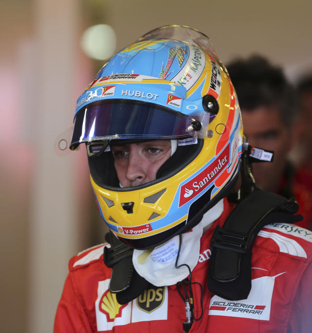 Ferrari driver Fernando Alonso of Spain prepares to get into his car during the first practice session for the Australian Formula One Grand Prix at Albert Park in Melbourne, Australia, Friday, March 14, 2014. (AP Photo/Rob Griffith)