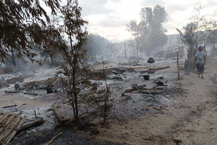 A resident walks past smoldering houses in the Kinma village, Pauk township, Magwe division, central Myanmar, Wednesday, June 16, 2021. Residents said people are missing after military troops burned the village the night before. (AP Photo)