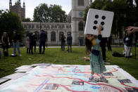 """Gabriella, the seven year old daughter of imprisoned British-Iranian Nazanin Zaghari-Ratcliffe, joins in a game on a giant snakes and ladders board in Parliament Square, London, to show the """"ups and downs"""" of Zaghari-Ratcliffe's case to mark the 2,000 days she has been detained in Iran, Thursday, Sept. 23, 2021. Zaghari-Ratcliffe was originally sentenced to five years in prison after being convicted of plotting the overthrow of Iran's government, a charge that she, her supporters and rights groups deny. While employed at the Thomson Reuters Foundation, the charitable arm of the news agency, she was taken into custody at the Tehran airport in April 2016 as she was returning home to Britain after visiting family. (AP Photo/Matt Dunham)"""