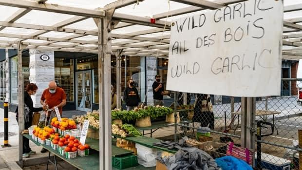 People shop at a distance at a ByWard Market vegetable stall May 10, 2021. The siges advertises garlic and there are also peppers and tomatoes at the stand.