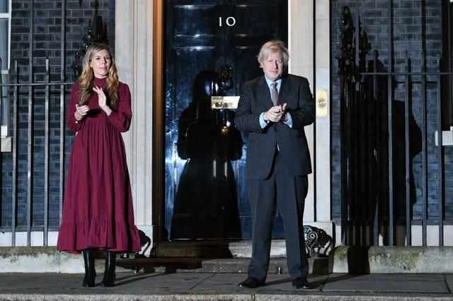 Prime Minister Boris Johnson and his partner Carrie Symonds stand outside 10 Downing Street, London, to join in with a nationwide clap in honour of Captain Sir Tom Moore, the 100-year-old charity fundraiser who died on Tuesday after testing positive for Covid-19