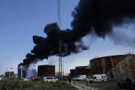Smoke rises from an oil facility in the southern town of Zahrani, south of the port city of Sidon, Lebanon, Monday, Oct. 11, 2021. Firefighters extinguished the huge blaze that broke out in a storage tank at one of Lebanon's main oil facilities in the country's south Monday after it sent orange flames and a thick black column of smoke into the sky. (AP Photo/Hassan Ammar)
