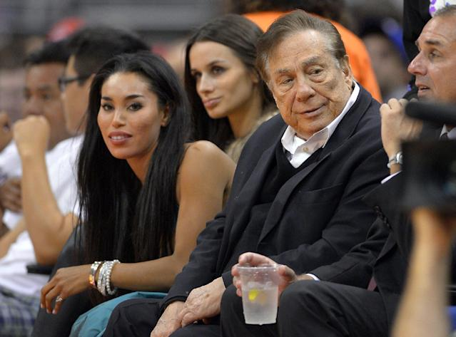 "In this photo taken on Friday, Oct. 25, 2013, Los Angeles Clippers owner Donald Sterling, right, and V. Stiviano, left, watch the Clippers play the Sacramento Kings during the first half of an NBA basketball game in Los Angeles. The NBA is investigating a report of an audio recording in which a man purported to be Sterling makes racist remarks while speaking to his Stiviano. NBA spokesman Mike Bass said in a statement Saturday, April 26, 2014, that the league is in the process of authenticating the validity of the recording posted on TMZ's website. Bass called the comments ""disturbing and offensive."" (AP Photo/Mark J. Terrill)"