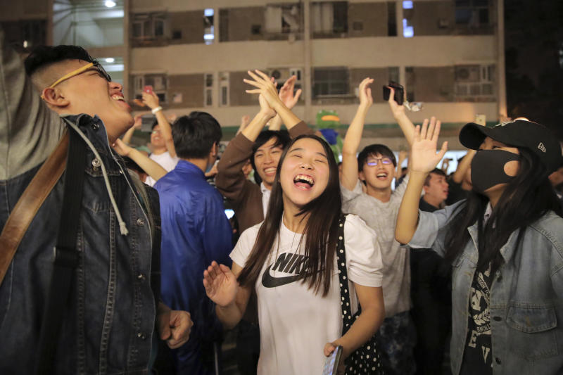 Pro-democracy supporters celebrate after pro-Beijing politician Junius Ho lost his election in Hong Kong, early Monday, Nov. 25, 2019. Vote counting was underway in Hong Kong early Monday after a massive turnout in district council elections seen as a barometer of public support for pro-democracy protests that have rocked the semi-autonomous Chinese territory for more than five months. (AP Photo/Kin Cheung)