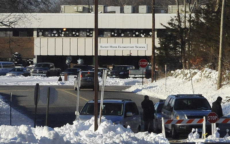 FILE - In this Jan. 3, 2013 file photo, police block the road at the entrance to the new Sandy Hook Elementary School on the first day of classes in Monroe, Conn. Three months after the Newtown massacre, children and teachers who survived remain on edge. Signs in the new school ask people to close doors softly and not to drag objects across the floor during school hours, in an effort to help keep students and faculty at the school as calm as possible. (AP Photo/Jessica Hill, File)