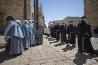 Priests wearing face masks march after Easter Sunday mass, in the Old City of Jerusalem, Sunday, April. 4, 2021. (AP Photo/Oded Balilty)