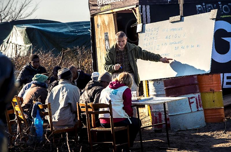 """Migrant children are taught at a makeshift school in the """"Jungle"""" camp in the port town of Calais, northern France, on February 16, 2016 (AFP Photo/Philippe Huguen)"""