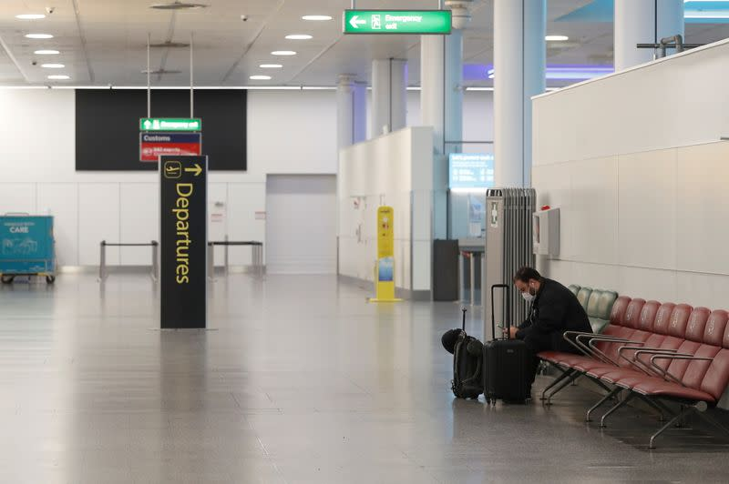 A passenger sits in an almost empty check-in area at Gatwick Airport, amid the coronavirus disease (COVID-19) outbreak, in Crawley