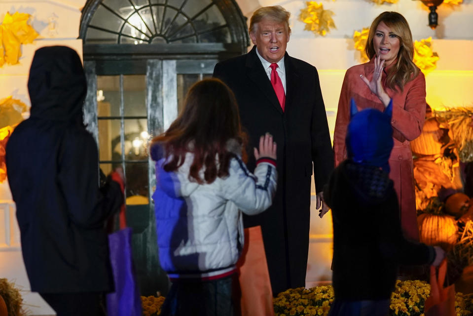 President Donald Trump and first lady Melania Trump greet trick-or-treaters on the South Lawn during a Halloween celebration at the White House, Sunday, Oct. 25, 2020 in Washington. (AP Photo/Manuel Balce Ceneta)