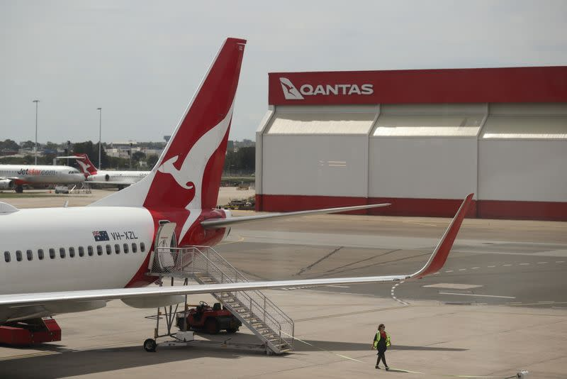 FILE PHOTO: A crew member walks from a Qantas plane at a domestic terminal at Sydney Airport in Sydney