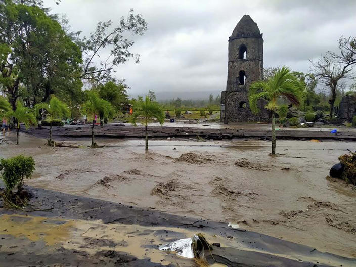 Floodwaters pass by Cagsawa ruins, a famous tourist spot in Daraga, Albay province, central Philippines as Typhoon Goni hit the area Sunday, Nov. 1, 2020. The super typhoon slammed into the eastern Philippines with ferocious winds early Sunday and about a million people have been evacuated in its projected path, including in the capital where the main international airport was ordered closed. (AP Photo/Alejandro Miraflor)