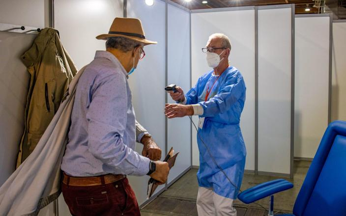 A worker checks in a visitor ahead of administering a vaccine at the Brussels Expo Covid-19 Vaccination Center in Brussels, Belgium, on Friday, March 5, 2021. - Olivier Matthys/Bloomberg
